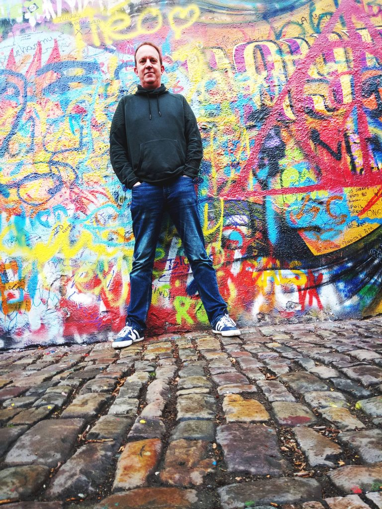 Jules Little standing in front of a graffiti wall